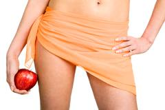 Image of feminine figure wearing orange pareo on hips and holding ripe apple in Stock Photos