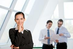 portrait of attractive business lady looking at camera with smile with men discu - stock photo