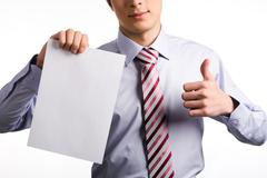 image of human hand keeping thumb up while the other hand holding blank paper - stock photo