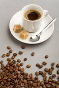 photo of cup of black coffee with two pieces of sugar and brown beans near by - stock photo