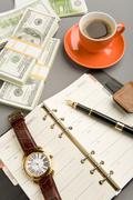 image of open notepad with fountain pen and watch on it and red cup of coffee wi - stock photo