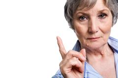 photo of elderly female with her forefinger pointed upwards on white background - stock photo