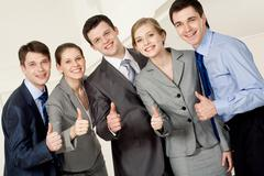 portrait of happy business partners looking at camera with smiles and showing si - stock photo