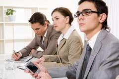 Photo of confident businesspeople listening attentively to speech at conference Stock Photos