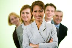 portrait of successful businesswoman looking at camera with several employees be - stock photo