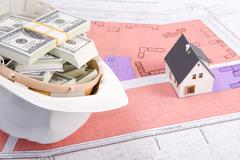 close-up of toy house model on blueprints with helmet full of dollars near by - stock photo