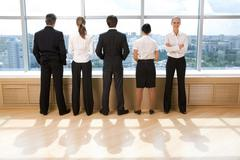 Rear view of business group standing in row and looking through window with thei Stock Photos