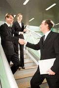 Handshake of business partners on the stairs of office building with smart woman Kuvituskuvat