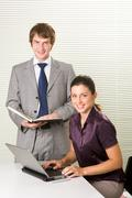 portrait of smart associates looking at camera with smiles while working in offi - stock photo