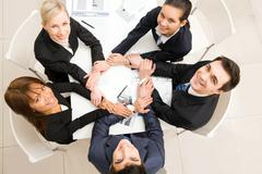 above view of business team with their hands making circle looking upwards - stock photo