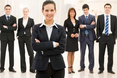 Portrait of confident well-dressed lady with business team at background Stock Photos