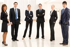 portrait of confident business group standing in semi-circle and looking at came - stock photo