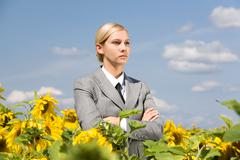 portrait of serious business lady with folded arms in sunflower field - stock photo