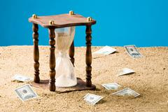 Image of hourglass and several hudred dollar banknotes near by on sand Stock Photos
