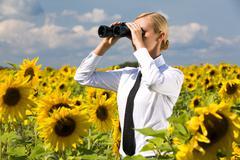 portrait of blond female looking through binoculars in sunflower field - stock photo