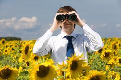 portrait of businessman looking through binoculars in sunflower field - stock photo