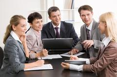 Photo of business group sitting at workplace and looking at successful woman Kuvituskuvat