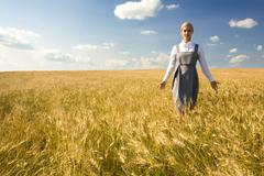 Smart female walking in wheat field against cloudy sky Stock Photos