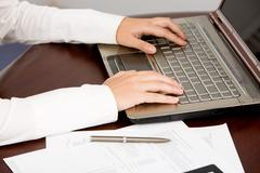 close-up of human hands over laptop keyboard during busy work - stock photo