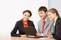 Photo of friendly business people sitting at table and looking forward during wo Stock Photos