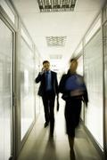 portrait of business people walking down long corridor in office building - stock photo