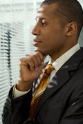 Serious businessman looking through venetian blind in office Stock Photos