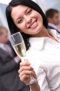 Portrait of beautiful female stretsching flute with champagne and smiling at cam Stock Photos