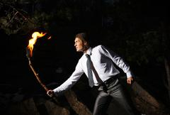 Image of brave man with burning stick in darkness Stock Photos