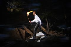 Image of brave man holding burning stick while moving in darkness Stock Photos