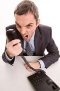 image of aggressive boss yelling into telephone receiver over white background - stock photo