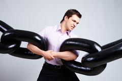 portrait of tense businessman with two sections of huge chain over grey backgrou - stock photo