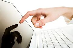 close-up of female hand with forefinger pointing at laptop screen over white bac - stock photo