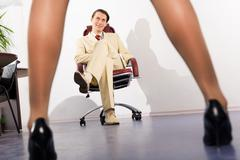 Image of slim female legs before businessman sitting in arm-chair and looking at Stock Photos