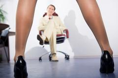Photo of feminine legs in high heeled shoes with sitting businessman at backgrou Stock Photos
