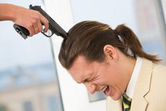 photo of desperate businessman shouting while having pistol on his head held by - stock photo