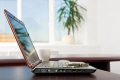 image of open laptop on table in the office with pen on keyboard - stock photo