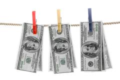 conceptual photo of dollars hanging on rope over white background - stock photo