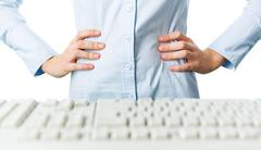 close-up of female keeping her hands on waist before computer keyboard - stock photo