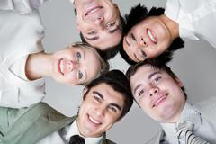 Below view of five friends looking at camera with their heads next to each other Stock Photos