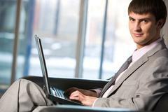 Handsome male typing on keyboard of laptop and looking at camera Kuvituskuvat
