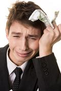 photo of grieving businessman with crumpled banknote in his hand - stock photo