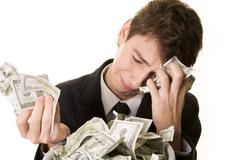 conceptual image of grieving young businessman over heap of crumpled dollars - stock photo