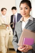 Image of pretty female worker holding folder and notepad Stock Photos