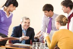 Group of successful managers communicating with senior boss at meeting Stock Photos