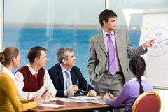 image of business group listening attentively to their young colleague making pr - stock photo
