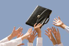 close-up of male hand holding briefcase surrounded by other people hands - stock photo