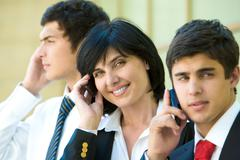 row of three agents calling by their mobile phone - stock photo