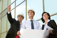 Image of worker showing something to customers on the background modern build Stock Photos