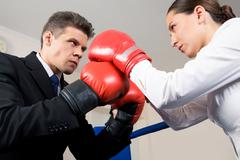 photo of aggressive business partners in boxing gloves fighting with each other - stock photo