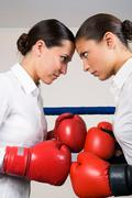 Photo of aggressive business women in boxing gloves fighting with each other Stock Photos